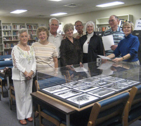 small group of former internees gather around display of Crystal City Internment Camp in University of Texas, San Antonio