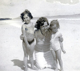 woman with two small children on the beach