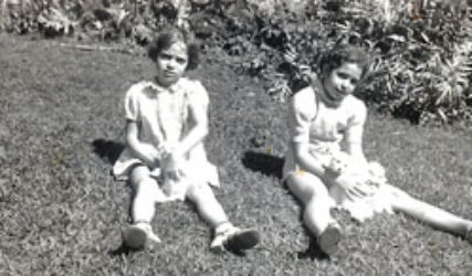 two young girls sit on lawn