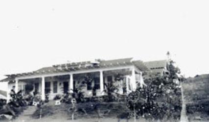 single-storied white house with veranda on a hillside