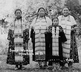 photo of 3 Native American women and a girl, dressed in ceremonial clothing