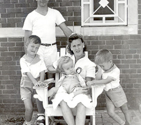 Father and 2 young sons stand; wife sits with baby on her lap-brick building in background