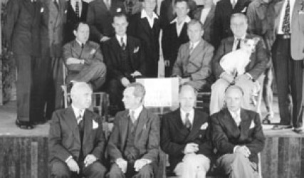 group of men, seated and standing on stage