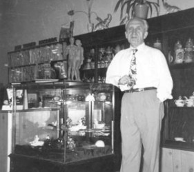 Mr. Greis leans on store case filled with items; shelves behind him hold other goods