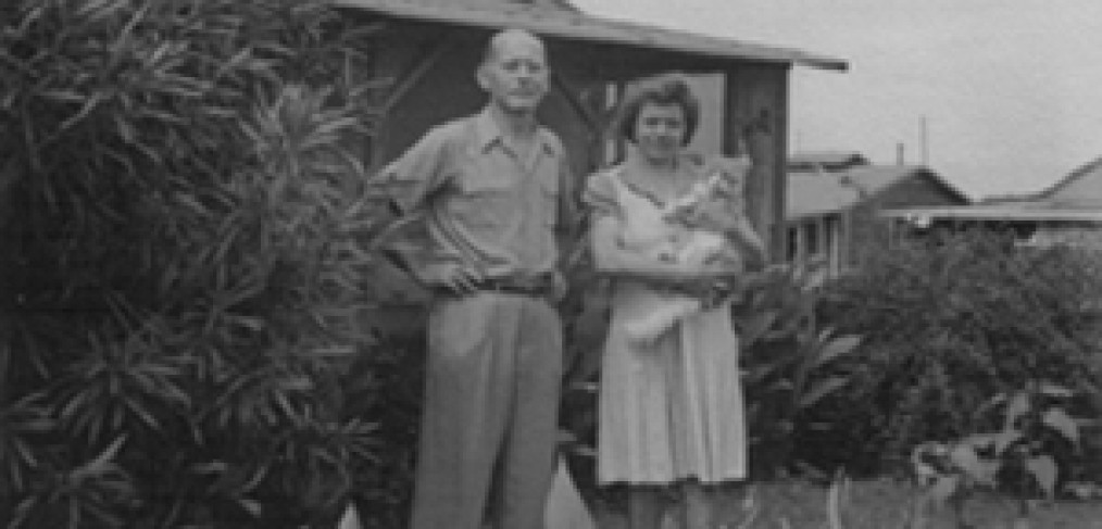the couple stands in front of their bungalow; she holds a cat