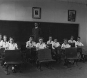 children at desks with teacher in the back
