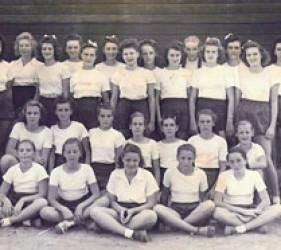 group of girls dressed in white tops, dark shorts
