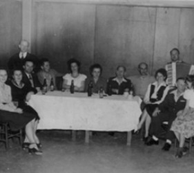 a group gather around a white clothed table