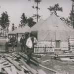 a pile of wood planks, men working, and square huts with tented roofs