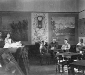 view of canteen, with 4 men seated and one man behind counter to left
