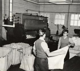 two men fold sheets