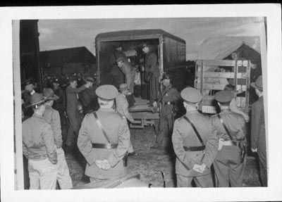 internees climbing out of truck back, watched by camp guards