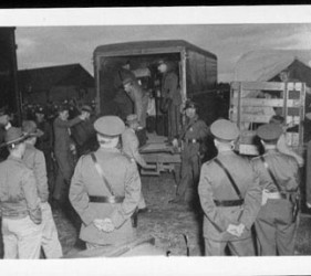 internees arriving by truck, with guards lined up in foreground