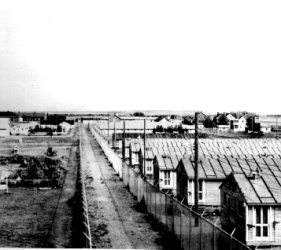 view of numerous barracks, with 2 barbed wire fences
