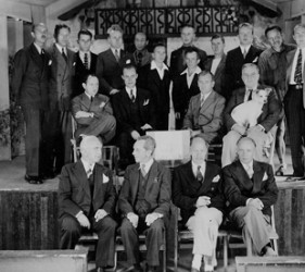 group of men on and in front of stage; one man holds small white dog