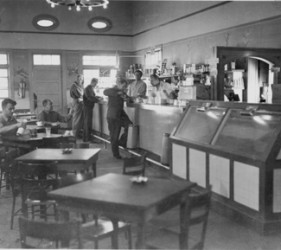 row of tables and a counter to the right; men seated and standing at the counter, with food