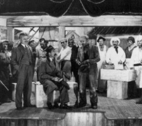 a group of men on stage, some dressed as women