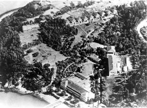 An aerial view of the Immigration Station, administration building in foreground, dentention barracks on right, hospital to the left, and Julia Morgan-designed employee cottages at the top of the photo. Source: California Department of Parks and Recreation.