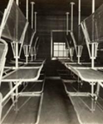 stacks of bunk frames in dark, cramped room