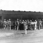 a number of men, some internees, some guards, in front of train car