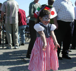 little girl with red, white, and blue dress and flags for Japan, Germany, and Italy in her hair