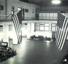 large hall with some seating areas and 2 large U.S. flags