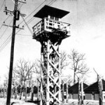 photograph of guard tower, with barbed wire and huts in background