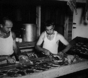 2 men preparing food in kitchen