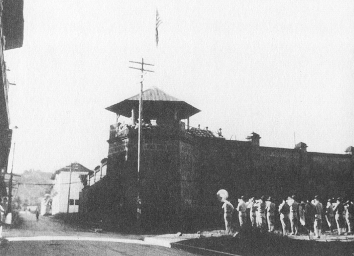 stone guard tower and fort walls, with group of men at right