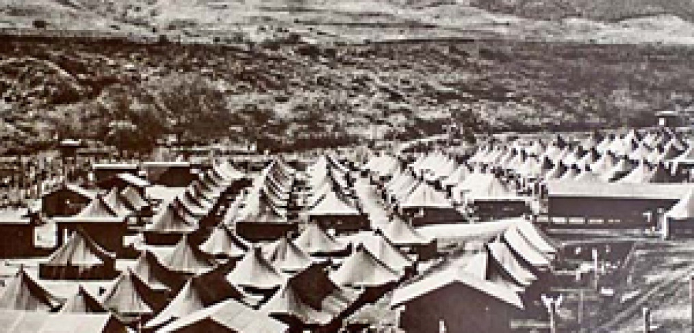 """overview of a tent """"city"""" behind barbed wire fences"""