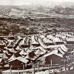 "overview of a tent ""city"" behind barbed wire fences"