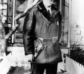 man in warm jacket and hat, with gun in holster and smoking cigarette