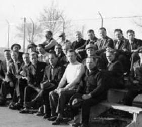 group of internees on small bleachers, with barbed wire fence behind them