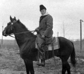 man on horseback with heavy coat and hat