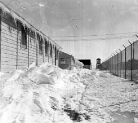 snow drifts and icicles along buildings and barbed wire fence