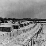 one story buildings in the snow with two barbed wire fences on perimeter