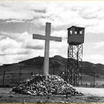 large cross, with guard tower and fence in background