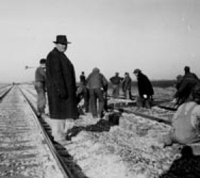 men working on railroad track; several men simply standing there, looking at them