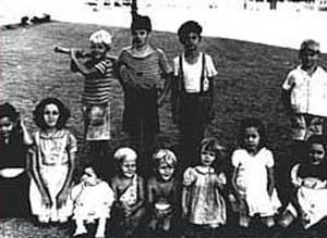 12 children of varying ages and dress line up for photo; one boy holds a stick like a bat