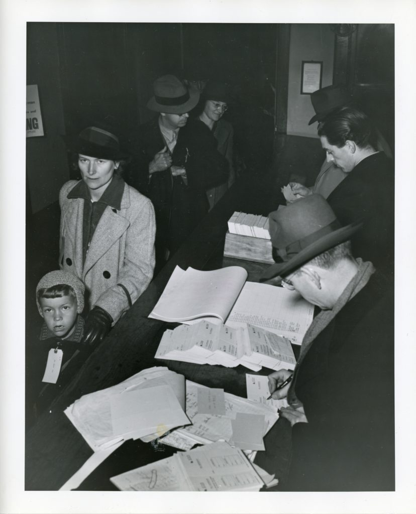 men at desk with paperwork, mother shepherds child past