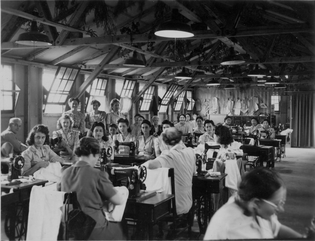women in large room, many sewing machines